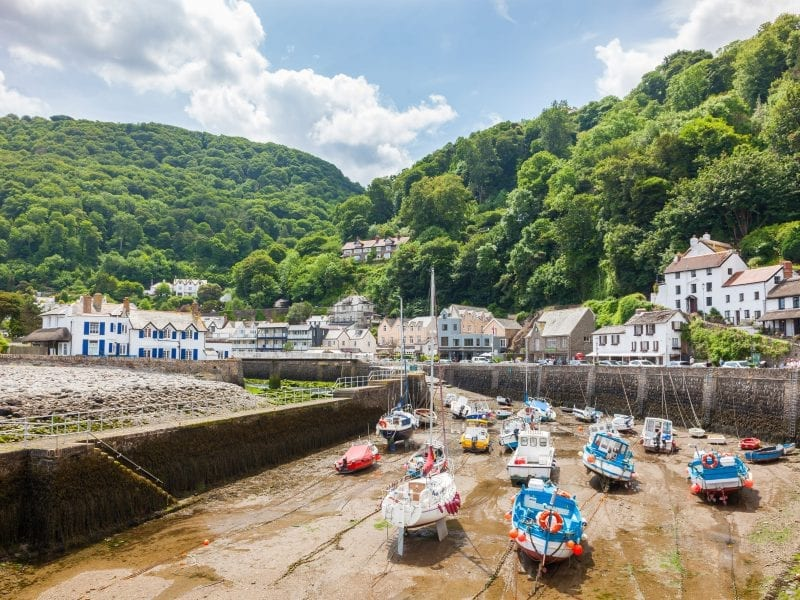 a picture of Lynmouth, a dry harbour with boats, surrounded by trees and white houses