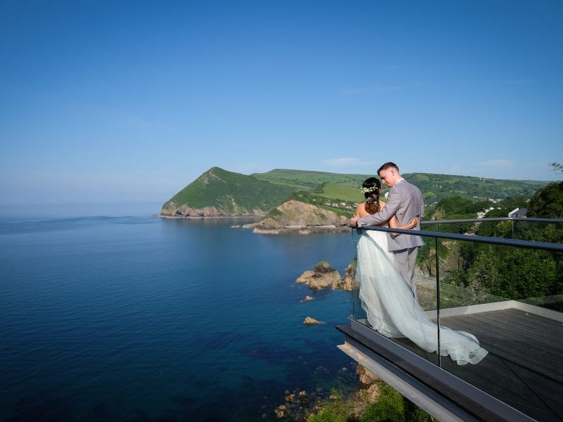 a picture of a couple holding each other at the end of a balcony with a sea background