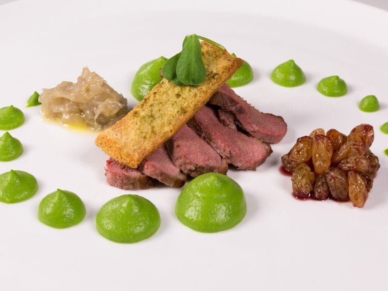 a picture of plate of meat with green garnish