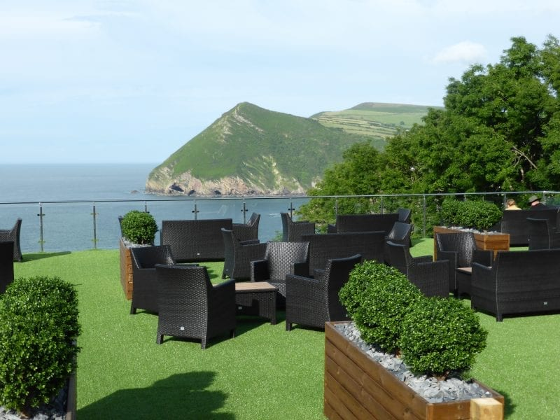 a picture of sandy cove hotel roof terrace with black chairs and a sea and cliff view in the background