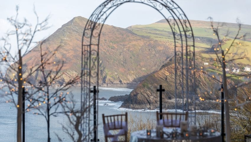 a picture of a laid table with an arch and cliffs and see in the background