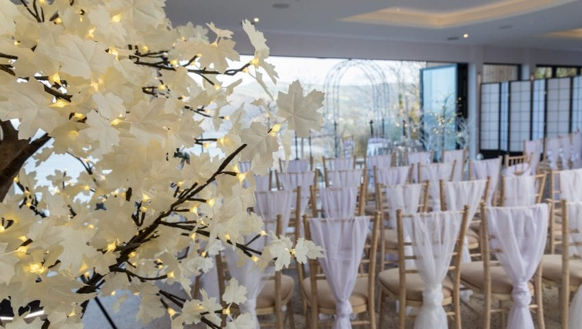 a picture of a room full of decorated chairs with a white floral light