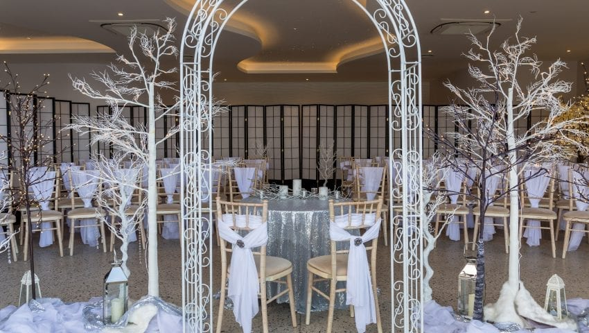 a picture of white arch with a laid dining room in the background, white decorative trees