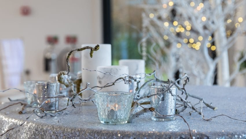 a picture of a silver glittery table with decorative branches and candles