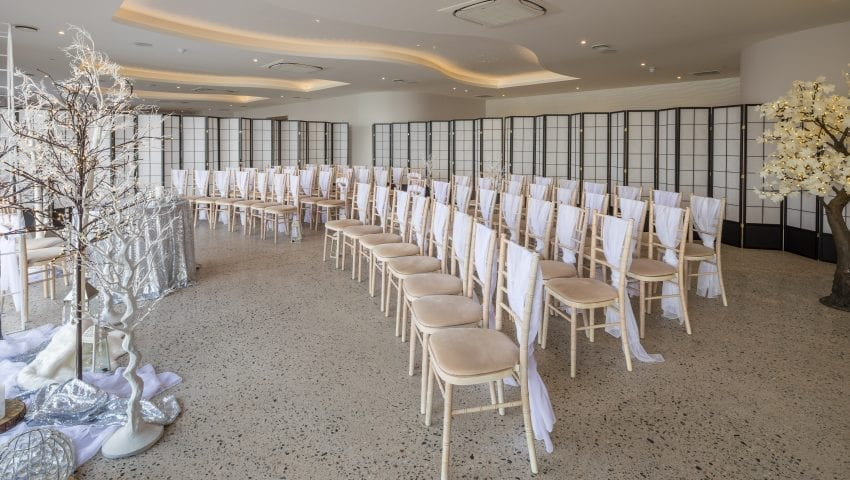 a picture of rows of chairs with decorative indoor trees