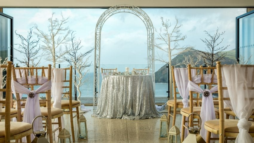 a picture of a white arch, a silvery glittery table, decorative indoor trees and a sea view in the background