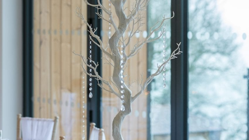 a close up picture of a decorative tree on a laid table with dangling beads
