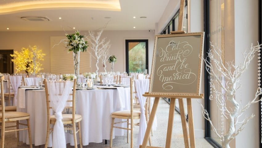 a picture of a wedding dining room with laid tables, decorative white trees with white dangling beads and a welcome sign