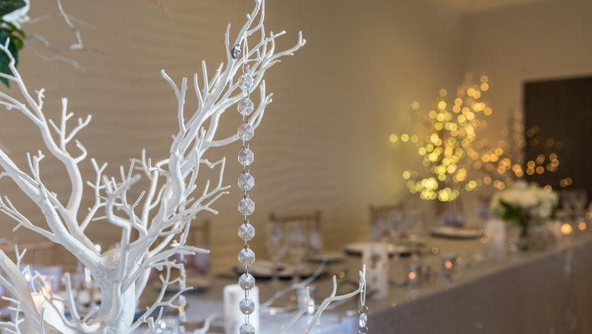 a picture of a close up of a decorative white tree with dangling beads and a laid top table in the distance