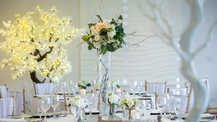 a picture of a laid wedding table with a centred floral arrangement in a vase