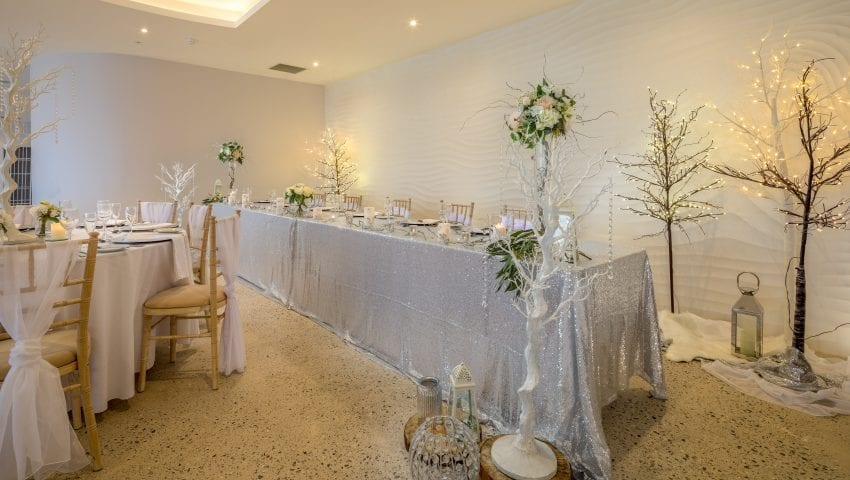a picture of a wedding dining room with laid tables, decorative white trees with white dangling beads, glittery tablecloth