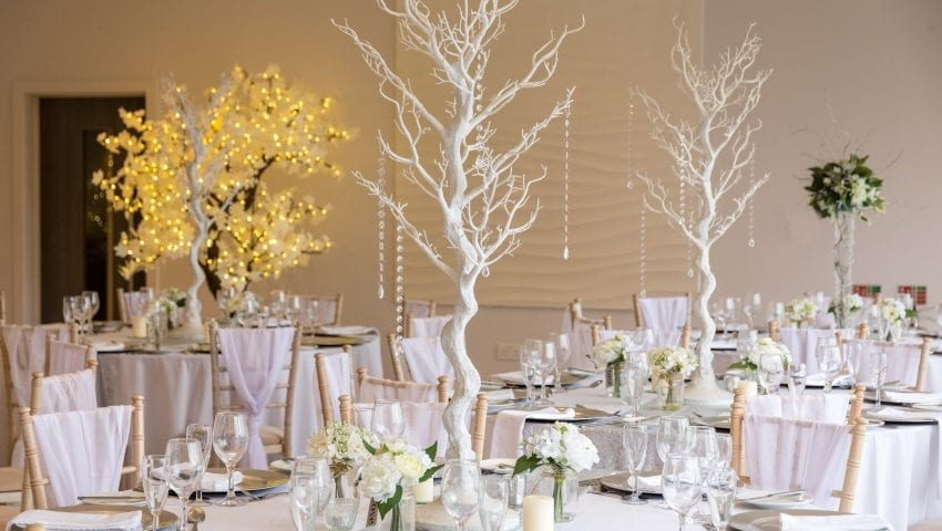 a picture of a wedding dining room with laid tables, decorative white trees with white dangling beads