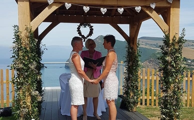 a picture of a couple at the altar with a sea view in the background