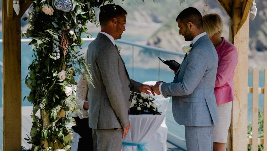 a picture of a couple at the altar under a floral arch
