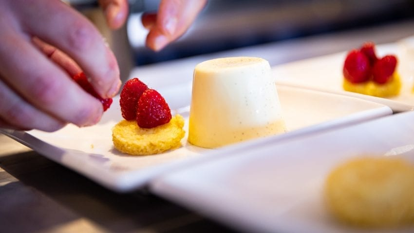 a picture of a close up of a chef decorating a pana cotta
