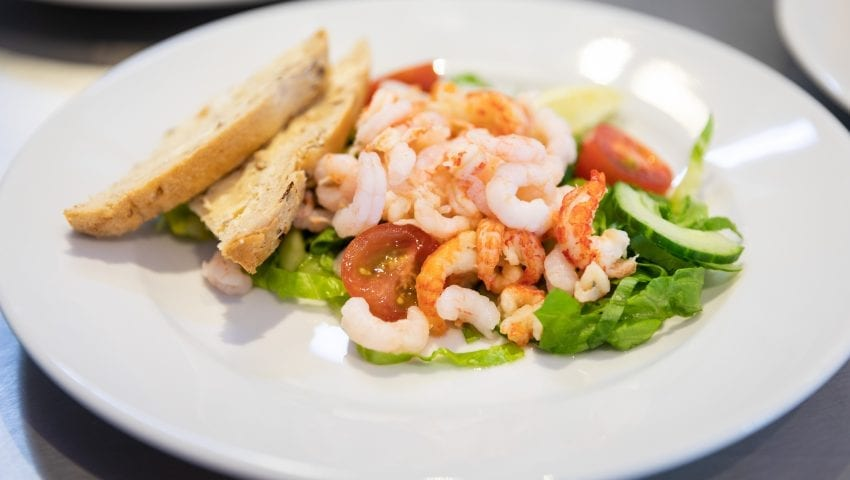 a picture of a prawn salad on a plate with slices of bread