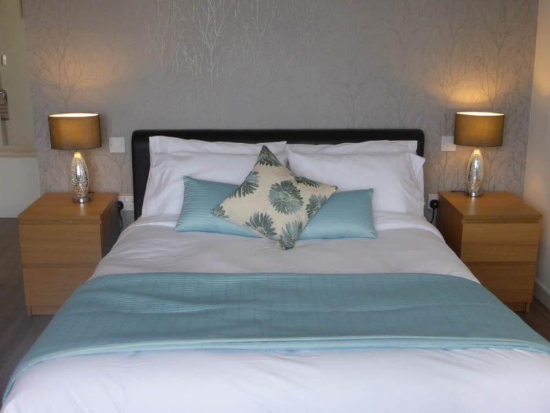 a picture of a bed with a pale blue throw, pale blue cushions and two gold lamps on bedside cabinets
