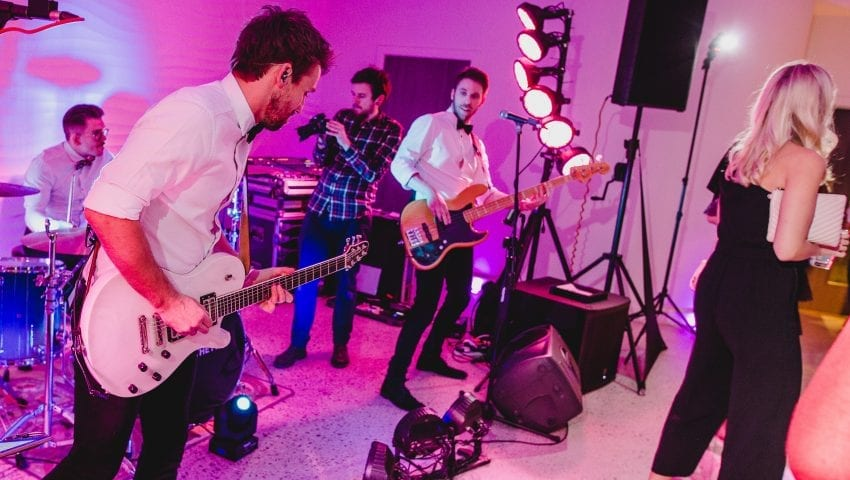 a picture of a band performing at a wedding venue in a pink tinged room