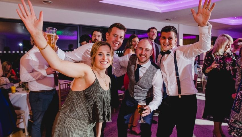 a picture of a group of people at a wedding posing for a photo with their hands in the air