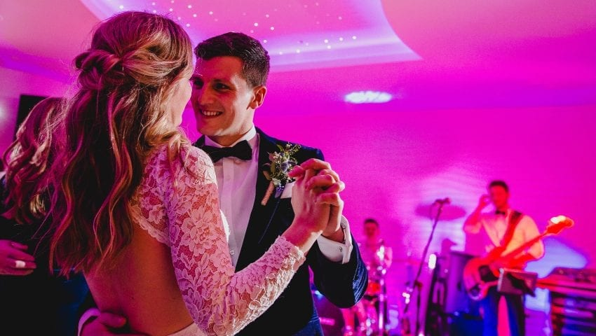 a picture of a couple dancing with a band in the background in a pink tinted room