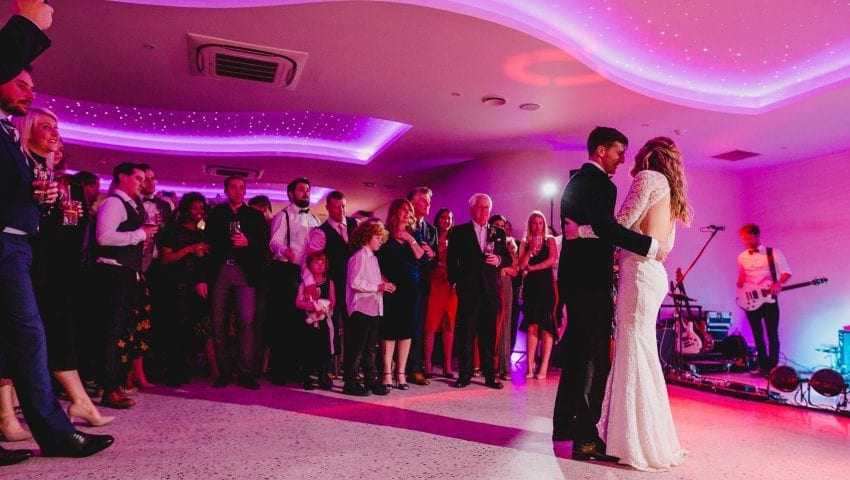 a picture of a couple dancing with a band and family in the background in a pink tinted room