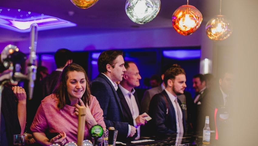 a picture of a women and three men standing at a bar with giant colour lights dangling down