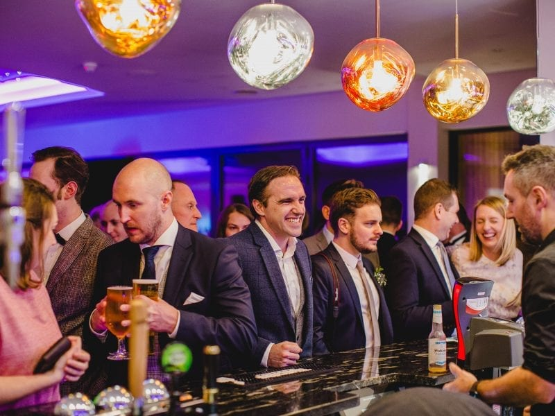 a picture of a row of people standing at a bar with giant colour lights dangling