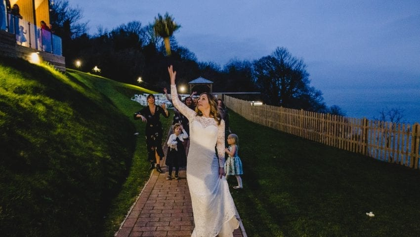 a picture of a bride throwing the bouquet to a group of women outside in the dark
