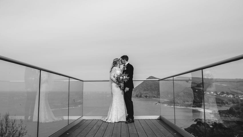 a black and white picture of a bride and groom kissing on a balcony with the sea in the background