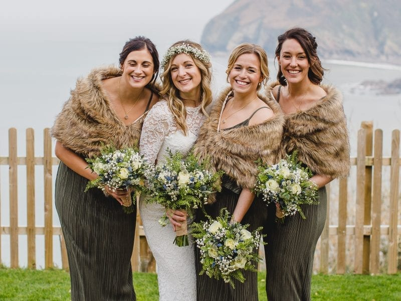a picture of 4 women holding bouquets posing with a sea in the background