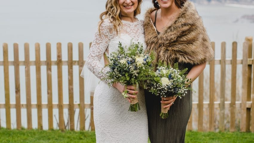 a picture of a bride and a women holding flowers smiling at the camera with the sea in the background