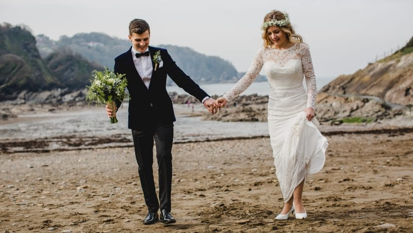 a picture of a bride and groom holding hands on the beach with the sea in the background