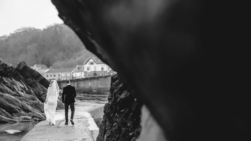 a black and white picture of a couple walking away from the camera on the beach