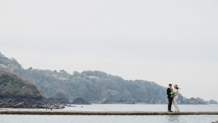 a picture of a couple stood on a path in between water with trees in the background