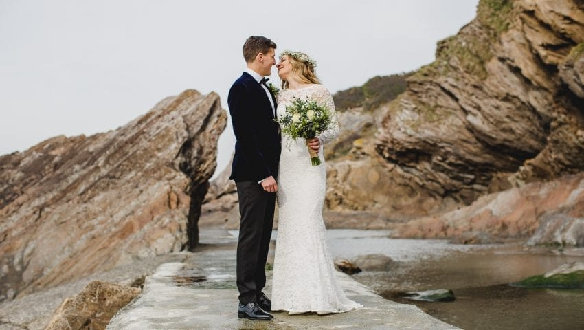 a picture of a bride and groom standing on a path looking at each other with cliffs in the background