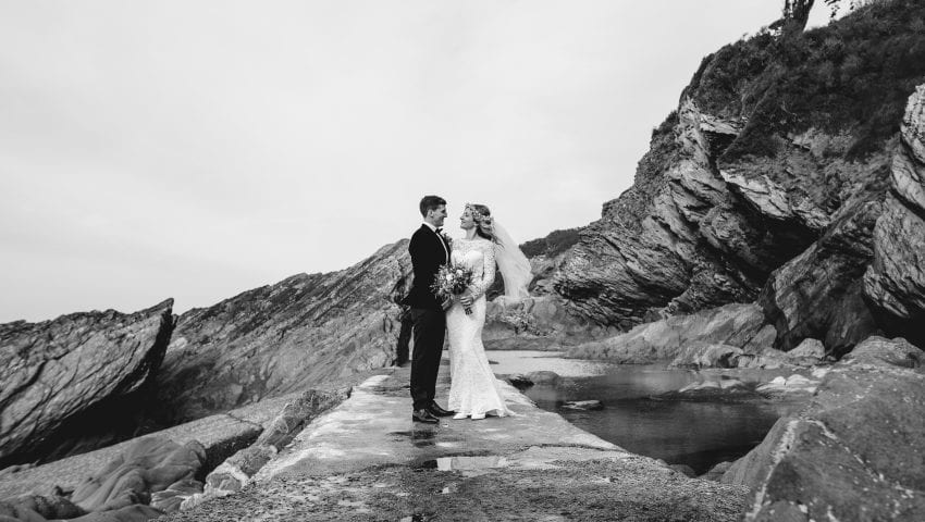 a black and white picture of a couple stood on a pathway with cliffs in the background