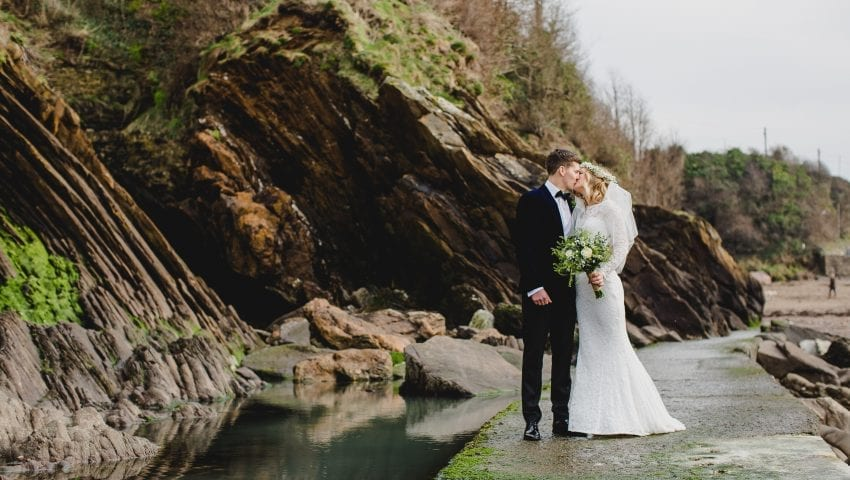 a picture of a couple holding each other kissing with a cliff and water in the background