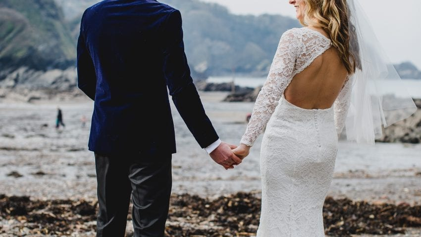 a picture of a bride and groom holding hands on the beach facing away from the camera