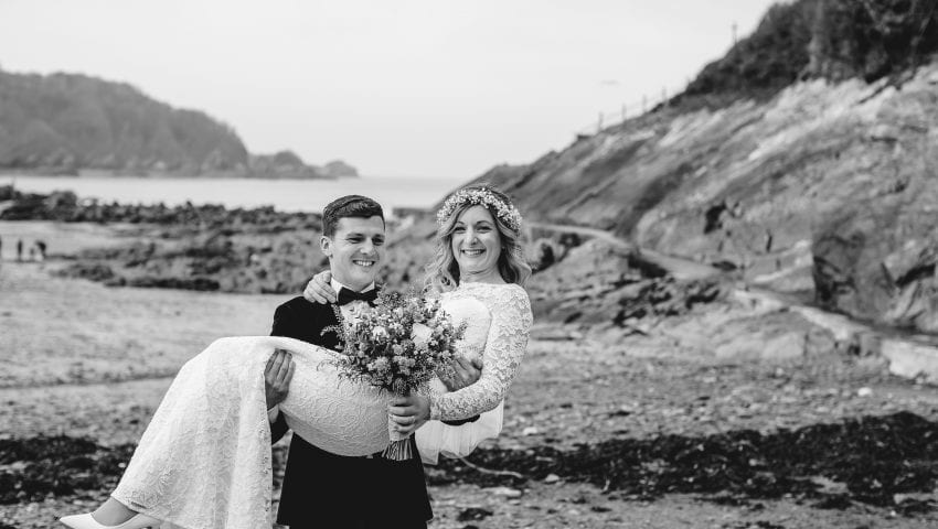 a black and white picture of a couple on the beach with the groom lifting up the bride holding a bouquet