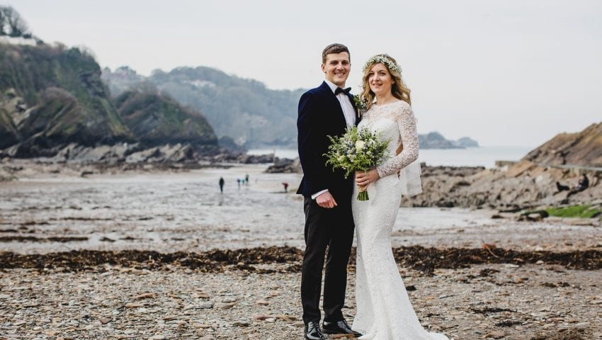 a picture of a couple stood on the beach facing the camera smiling
