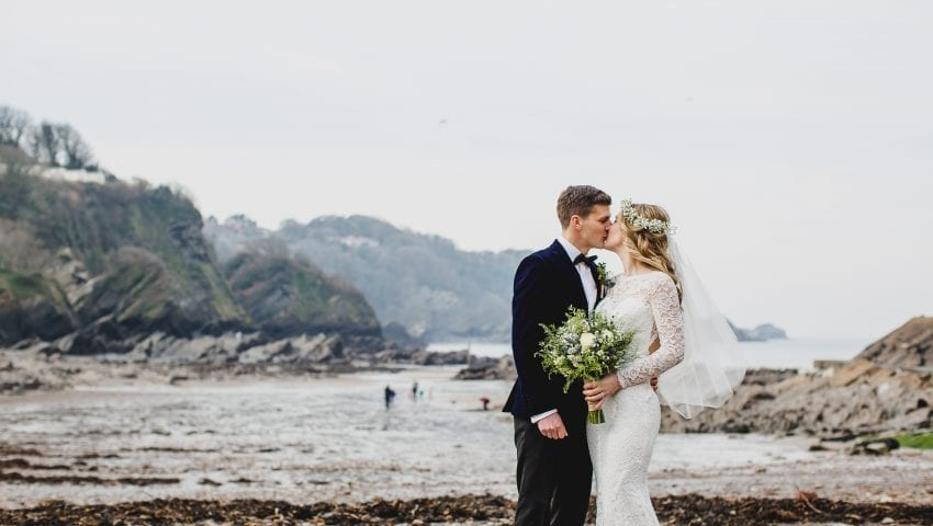 a picture of a couple kissing on the beach
