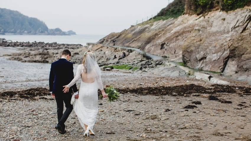 a picture of a couple walking on the beach away from the camera