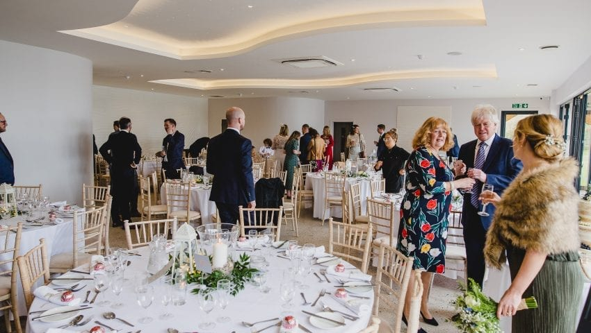 a picture of a wedding dining room with laid tables and family stood around