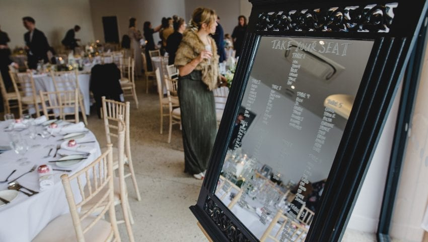 a close up picture of a mirror table seating plan with laid tables in the background with people in the background