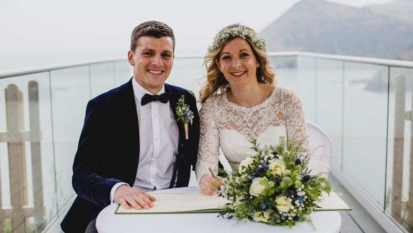 a picture of a couple smiling at the camera while signing the register with the sea in the background