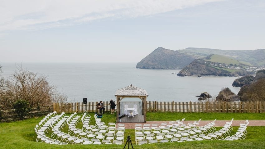 a picture of a wedding set up outside with chairs and the sea and cliffs in the background