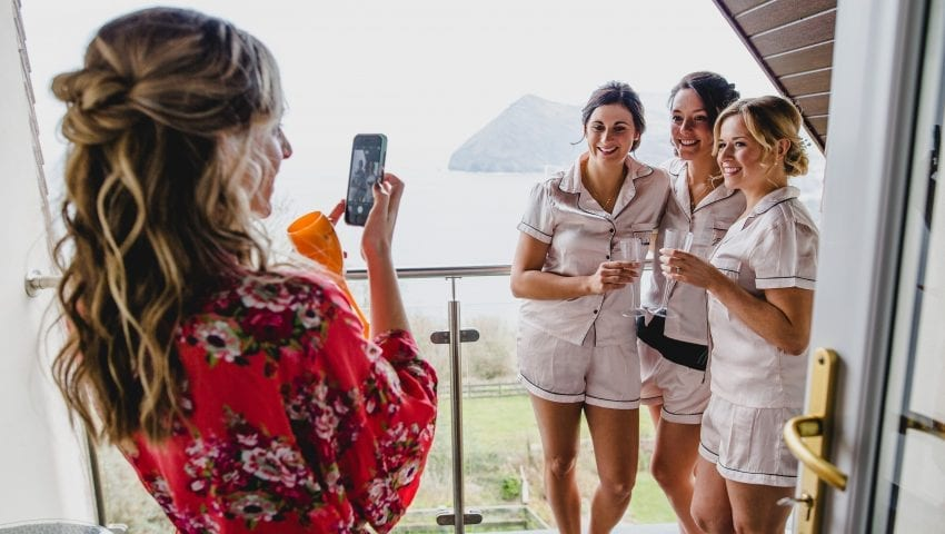 a picture of a woman taking a photo of three women on a balcony