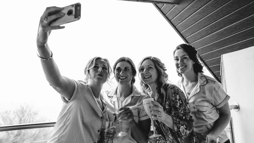 a black and white picture of four women taking a selfie on a balcony