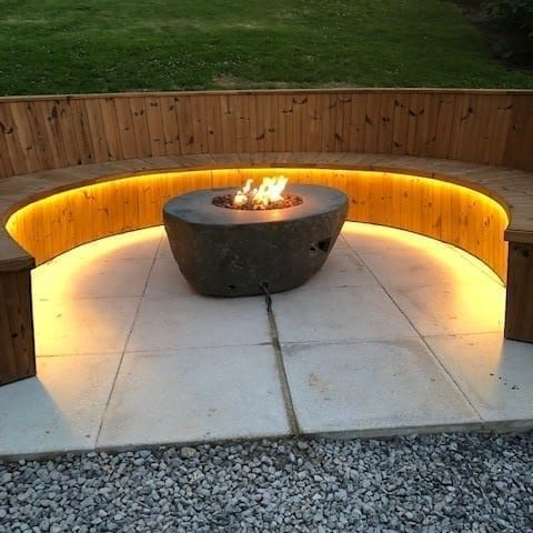 a picture of a fire pit with a surrounding wooden bench