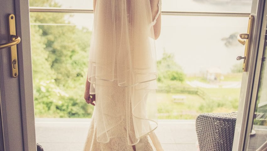 a picture of a bride stood on a balcony facing out to sea